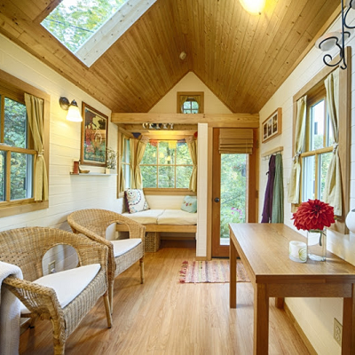 This tiny house on wheels looks so inviting! Great room chairs and a window nook are easy places to relax, and the table may be used for all different reasons. (Bayside Bungalow)