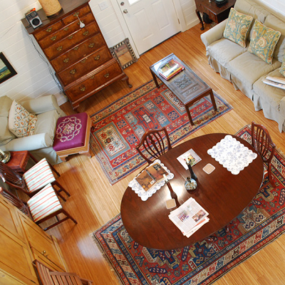 Looking down from the sleeping area, this great room features plenty of seating, a dining table and a large cabinet. Two rugs pull the traditional look together. (Kanga House)