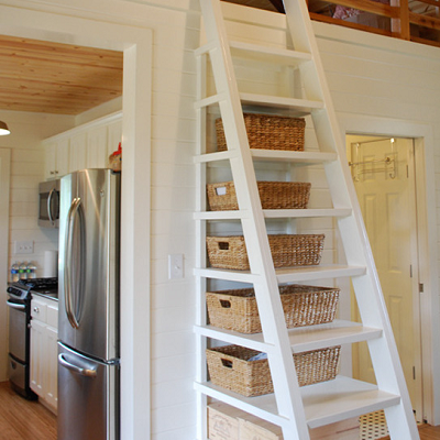 This ladder accesses the bedroom area and also provides storage shelves. It's permanently built into a 16'x30' cottage near Blanco, Texas. (Kanga Room Systems)