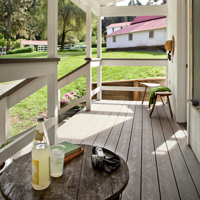 With a farmhouse look, you find a full porch that measures 90 sq. ft. Note the practical, long lasting trek deck for this wet climate. (Houzz.com)