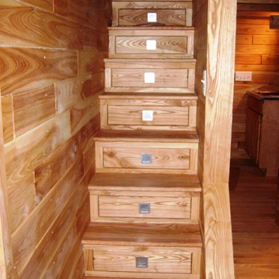 In this tiny house, built in Minnesota, well-crafted stairs look like mission furniture with separate storage drawers. (Tiny Green Cabins)