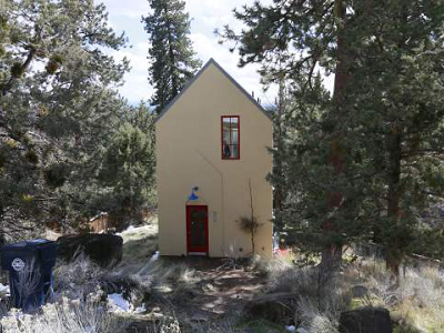 """""I've had people knock on the door, wanting to see this house,"" says Gary Beaudoin, owner and builder of a bright yellow and red-trimmed storybook home. Located in Bend, OR, the cutie measures 875 sq. ft. (Bend Bulletin)"