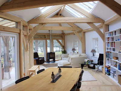 Devon's great room reveals strong bones through its interior wood trusses. The home is well-used for living, dining and also gazing at the views. There are plenty of bookshelves against one wall, as a terrific bonus. (Carpenter Oak)