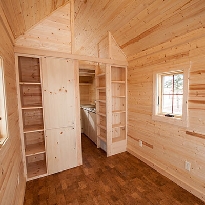 Imagine how you would decorate and make this empty great room your own. Besides the multi-use space, there's shelving and the loft entry in view. (Tumbleweed Houses)