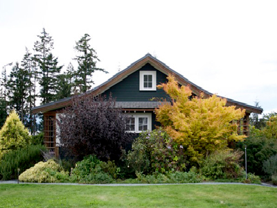 A traditional, yet new, small cottage beckons you with all its quiet charms. The curved roof-line, woodsy green color, white and natural wood accents bring the home together. Gilann Ridge is well-sited and landscaped in Washington State. (Ross Chapin)