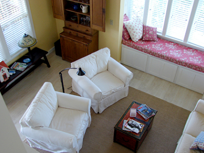 In Gilann Ridge's great room, you see a very efficient use of space with a built-in nook, side bench, well-proportioned chairs and love seat. Its yellow paint, white, tan and wood decor complement the exterior. (Ross Chapin)