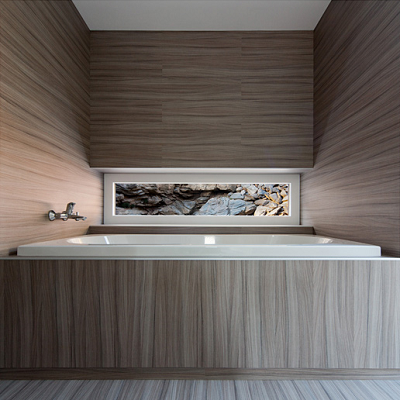 The spa bath is placed symmetrically in the enclosure, with warm colors that create a peaceful escape. (Hideg House)