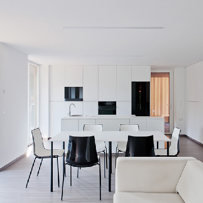 This white great room offers space to sit, cook and dine. Black appliances and chair backs create nice contrast. (Hideg House)