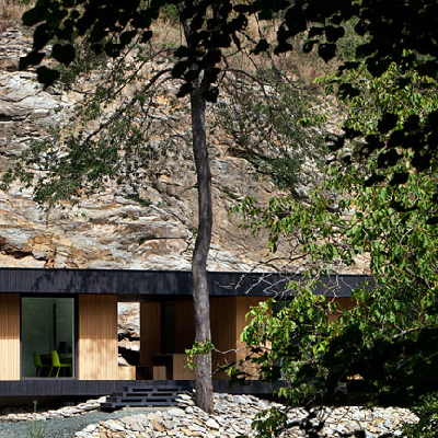 A rectangular modern, with birch siding and nice glass windows, is sited on an old quarry hillside. (Hideg House)