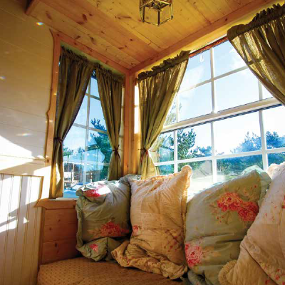This pretty nook, surrounded by windows on three sides, is the owner's favorite part of her home. (Little Yellow Door)