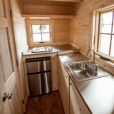 This new home includes a full galley kitchen in the back, with plenty of counter and storage space. Behind the door is the bathroom. (Tumbleweed Houses)