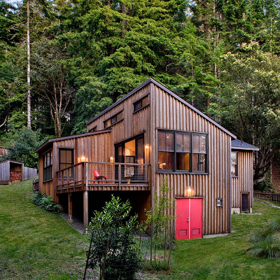 A SF Bay Area architect designed this modern cabin to feel much larger than its footprint thanks to a wide deck, soaring ceilings, large windows, and strategically placed built-ins. It has two bedrooms and one bath, in 840 sq. ft. (Cathy Schwabe)