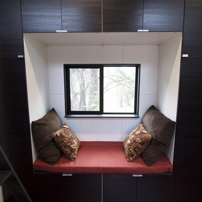 The hOMe's great room features a cozy alcove, easy for relaxing or watching TV across the way. (hOMe, Tiny House Build)