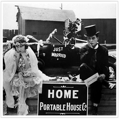 Newlyweds receive a house kit with building directions, and don't look too thrilled at the work ahead. (Sales on Film)