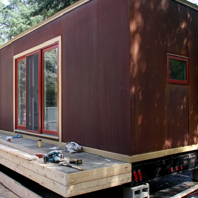 The deck gets assembled, raised up and placed alongside the tiny house. (Palo Alto Weekly)