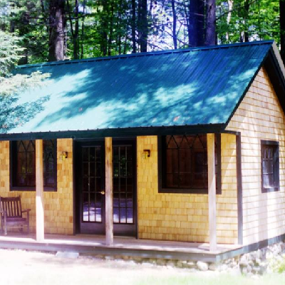 This cabin greets you with formal french doors, multi-paned windows and cedar shake siding. (Jamaica Cottage)