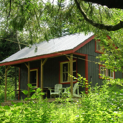The Vermont cottage looks exactly right in these woods, painted classic green. (Jamaica Cottage)