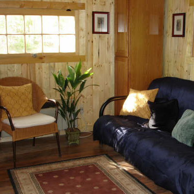 This cheery interior is decorated for comfort, including cabinet storage and a futon for overnight guests. (Jamaica Cottage)