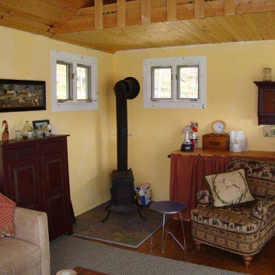 See the stove to keep warm, seating area and hint of kitchen counter. (Jamaica Cottage)