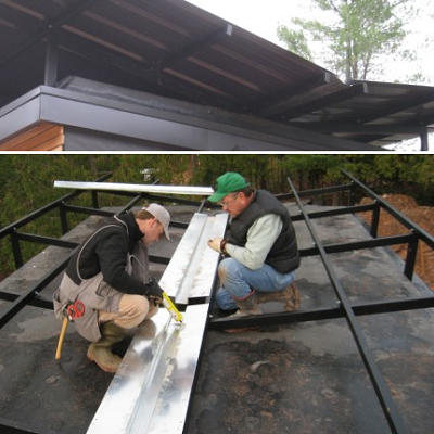 See the butterfly or V-shaped roof, on top, almost ready to collect raindrops. Below, the roof gutter is getting installed as part of the system. (Revelations Architects)