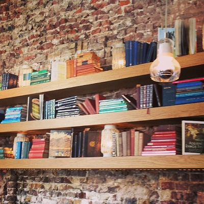 A few pieces of wood serve as nice bookshelves in a smaller home. Yes, people organize books by color. (Fever London)