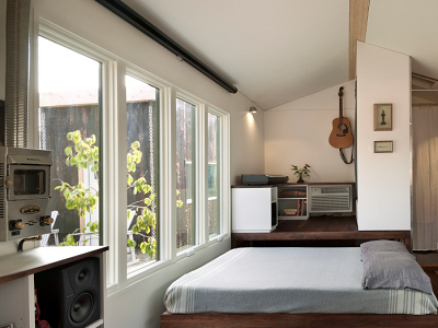 """SLEEPING, DC - """"The 5′x7′ office/storage area sits atop the bed platform. There is also a 5′ full width closet. The full or queen size bed hides under the platform, and easily slides out from underneath."""" (Minim Homes)"""