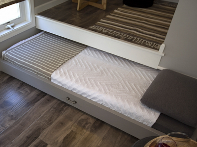 "SLEEPING, NY - ""The bed slides out for sleeping, but hides away under the office space when not in use."" In this close-up, the full bed is partly rolled out. Our homeowners know that sliding it away is their first daily task. (Tiny House Nation)"