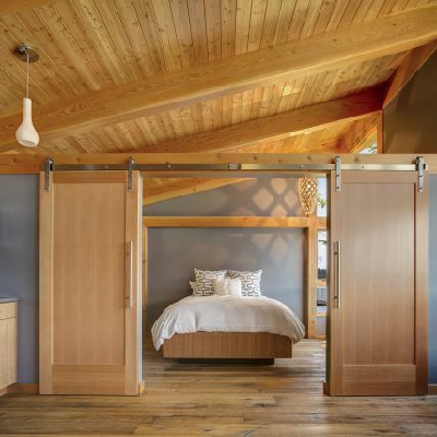 The bedroom is accessed through modern-day, sliding barn doors. It takes up one wing, with plenty of room as well as open views towards the lake. (Fine Homebuilding)