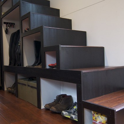 With an artful and geometric arrangement of open shelving beneath the stairs, storage gets maximized in this house on wheels. (hOMe, tinyhousebuild.com)