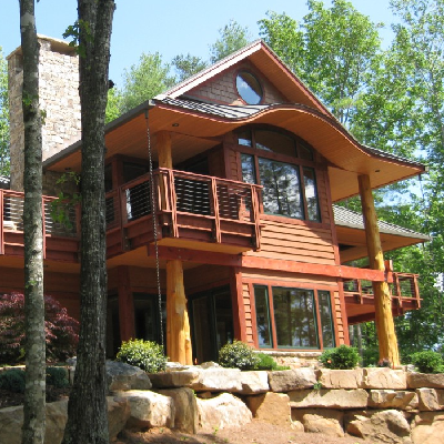 North Carolina Exterior - This refuge honors nature and gets nestled into its setting by incorporating log, cabin, Prairie and Japanese house style elements. With extensive glass windows, the place looks inviting from a small hill. (Fine Homebuilding)