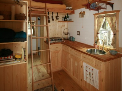 Country Little L with custom wood slab counter and cabinets. Appliances include a marine stove top, and small fridge under house. It doesn't have an oven or dishwasher. (Little Yellow)