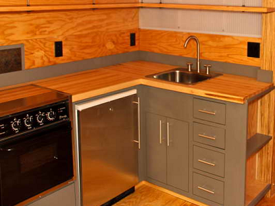 Hip Little L with a plywood and metal look. Appliances include a flip-up range top, oven and little fridge. It lacks a dishwasher. (Yestermorrow, Relax Shacks)