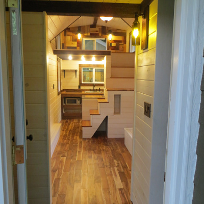 Peeking inside the Robin's Nest, we see its great room, kitchen, bathroom door to right and loft ahead. (Brevard)