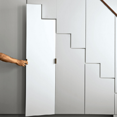 In a Brooklyn apartment, under-stair storage is hidden within a sleek, white wall integrating the staircase. Kitchen items get stored within these walls. (Dwell)