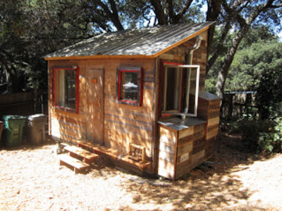 This old-fashioned tiny house sits on verdant hillside. It's a secondary unit on a city lot. (Oakland Tiny House)