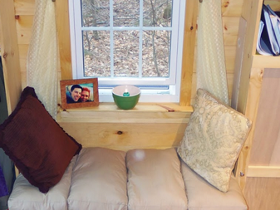 Sating nestled between shelves and a large window has become a favorite place to lounge. (Another Tiny House Story)