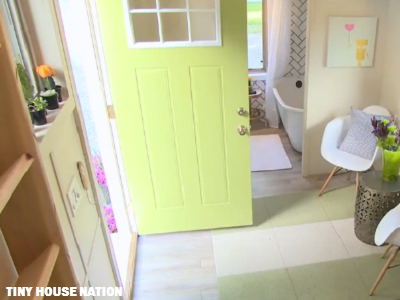 We love the transition, from the chartreuse entry door to the calm seating area. Also notice the bathroom, with herringbone tiling and a traditional tub. (Tiny House Nation)