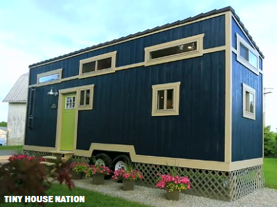 This modern home, painted an energizing blue, features a sloped roof and plenty of light shining through highly-placed windows. (Tiny House Nation)
