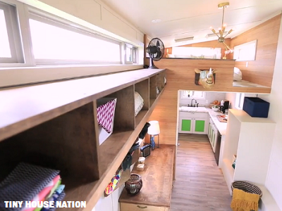 It fits: a U-shaped kitchen, sleeping loft and expandable dining table. The table even becomes a quilting zone, with one sewing maching and materials hidden there. (Tiny House Nation)