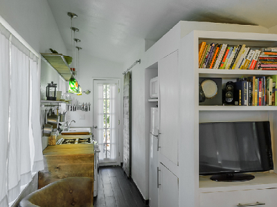 HOUSE - Notice the light and bright interior, looking towards the kitchen area and storage. The owner lives in this house on wheels with her beau, newborn and dog. (Minimotives.com)