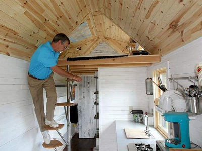 """Henry Camosse, father of Francis Camosse, climbs the stairs to the loft of his son's tiny house in Charlton,"" says the Worcester Telegram. (Photo by Paul Connors)"