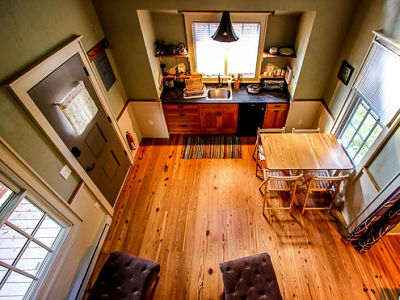 Here;s the Blue Sky great room and kitchen, looking down from a second, lofted sleeping area. (hobbitatspaces.com)
