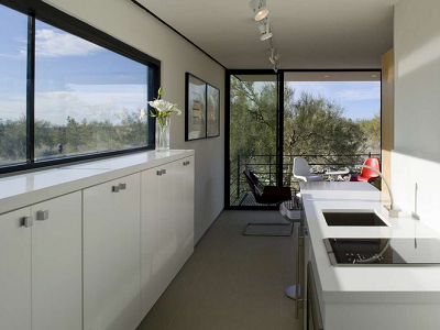 DESERT HOUSE: Interior space is arranged simply, with a galley kitchen leading to open seating and an outdoor deck. Behind the camera is another deck and separate sleeping quarters. (ModFabTM, Architizer)